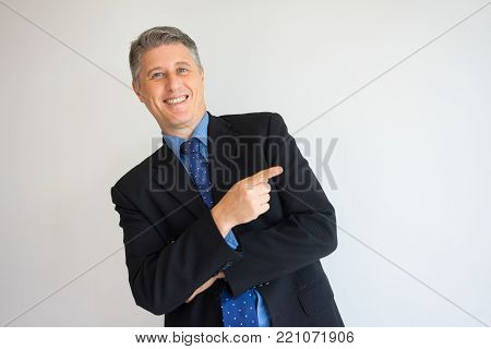 Closeup portrait of smiling middle aged speaker pointing finger aside presenting new idea. Top manager mocking at inexperienced young colleagues. Advertising, presentation or humor concept