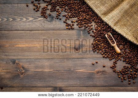 Fresh roasted coffee beans in scoop near canvas on dark wooden background top view.