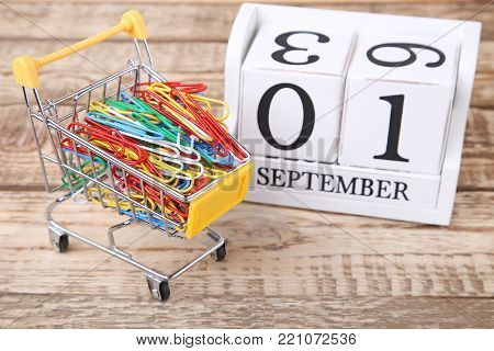 Shopping Cart With Paperclips And Calendar Cubes On Wooden Table