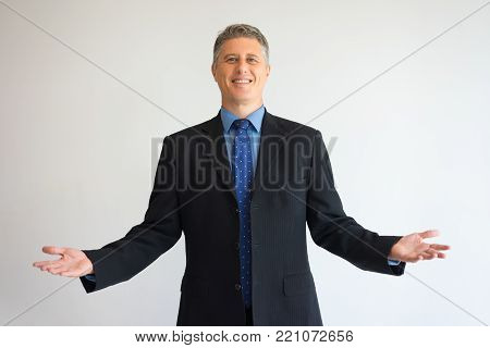 Portrait of broadly smiling CEO in suit with spread hands. Middle aged businessman welcoming partner. Business communication and welcoming concept.