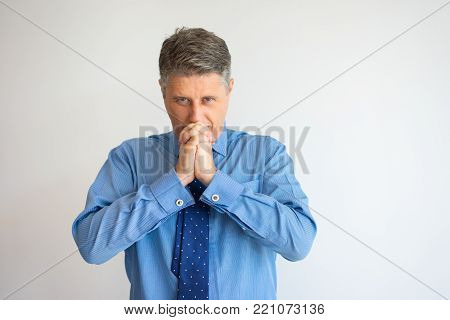 Closeup of tense middle aged Caucasian man covering mouth with clasped hands and praying. Businessman feeling regrets. Business and failure concept
