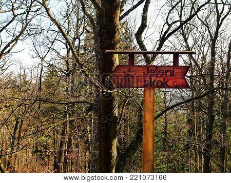 KARLOVY VARY, CZECH REPUBLIC - MARCH 14, 2014: The pointer to Jeleni Skok Rock near the Diana tower. Forest landscape, sunny spring day