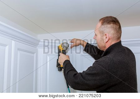 Construction worker using brad nail air gun to Crown Moulding on white kitchen wall cabinets framing trim, with the all power tools