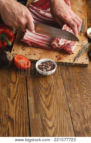 Man cutting rack of lamb on wooden board at restaurant kitchen. Chef preparing fresh meat for cooking. Modern cuisine backgroung with herbs and meat with copy space