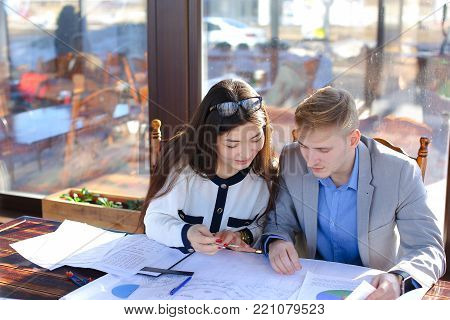 Students calling professor by smartphone to ask about architecture project. Boy and girl drawing with divider and ruler at cafe. Concept of preparing home task and drafting.