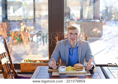 Businessman enjoying eating hamburger and French fries with sauce. Young man wears grey jacket with blue shirt and smart watch. Concept of satisfaction and fast food lunch.