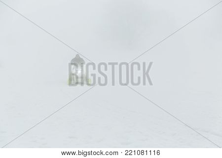 Snowmobile rider goes from a mountain in foggy weather.