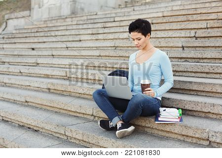 Concentrated student girl sitting on stairs working with laptop, drinking coffee, preparing for exams, having rest in university campus. Technology, education and remote working concept, copy space