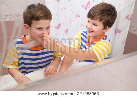 Older brother helping to clean the nose for younger brother in the bathroom with mirror