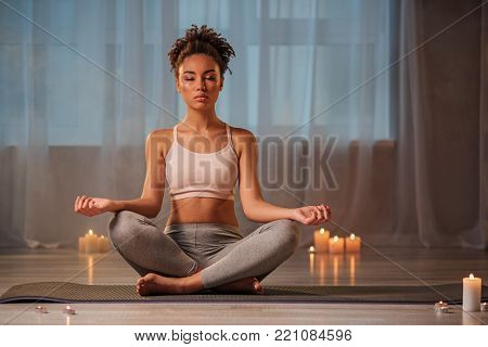 Full length portrait of concentrated young woman meditating in cozy room. She is sitting in posture with closed eyes