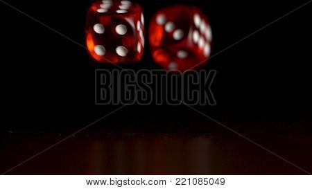 Red dice fall on black background. Casino concept. Two playing red dices on wooden table with dark background.
