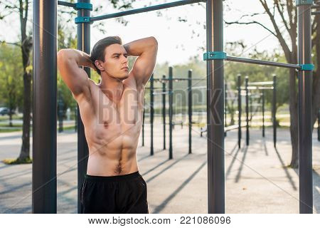Fitnes man posing on street fitness station showing his muscular body,