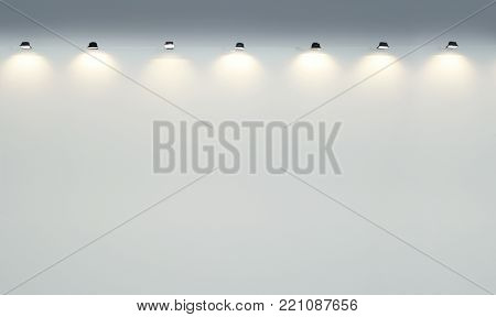 Abstract background of a wall of an empty gallery wall with many illuminated spotlights