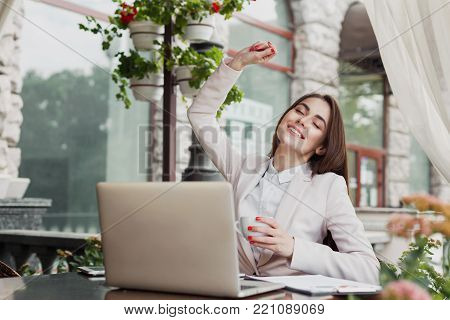 Happy excited businesswoman celebrate victory with arm raised in the air. Winner, successful caucasian woman outdoors sitting at summer terrace cafe, lifestyle portrait