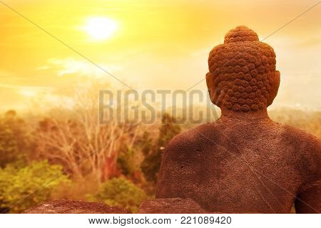 Sculpture of Buddha on a night sky background and moon. Artistic image. Buddhism concept.