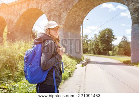 Young hitchhiker woman with backpack standing near old viaduct. Tourist backpacker girl in scenery country side