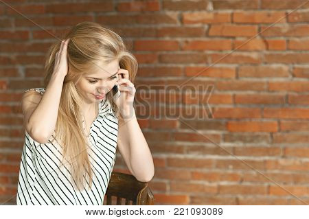A blonde girl is calling by the phone against a brick wall background, calling the apartment repair service. Advertising of construction services.