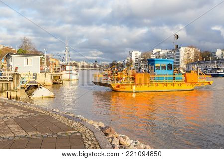 TURKU, FINLAND- November 01, 2013: Small ferry connecting the banks of the Aura River. In the background the cathedral in the city of Turku, the oldest city of Finland