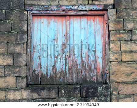 decaying blue painted shutters with rotting wood in a derelict abandoned house