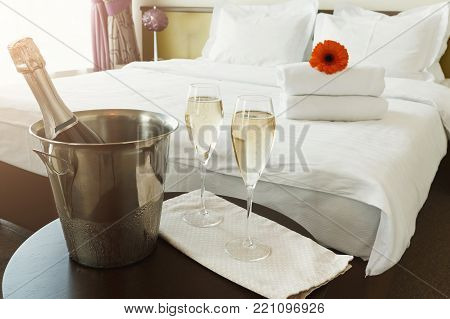 Two glasses of and champagne in ice bucket in hotel. Romance, room service, relax concept, copy space