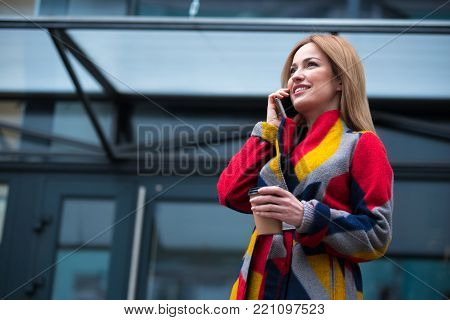 Low angle portrait of beaming lady telling by phone while drinking mug of coffee in street. Conversation and beverage concept. Copy space