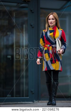 Full length portrait of cheerful female in colorful coat situating in street. Anticipation concept