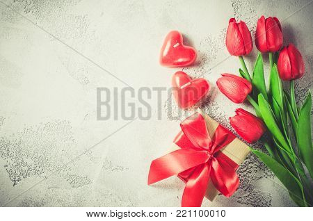 Bouquet of red tulips, gift and candles in the form of hearts on white background. Spring background. Greeting card for Valentine's Day, Woman's Day and Mother's Day. Top view, copy space.