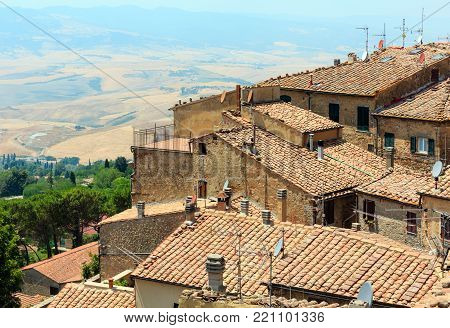 Summer ancient walled mountaintop town Volterra and farmland below, Pisa province, Tuscany, Italy.