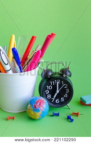 Back to school concept with stationery. School supplies on green background in pop art style. Schoolchildren and students studies accessories with clock and globe.