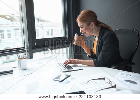 Side view beaming businesswoman tasting cup of hot beverage while typing in laptop. Job concept
