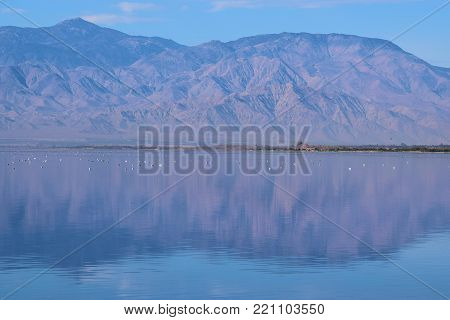 Lake surrounding barren mountains which is reflecting on the calm smooth water taken at the Salton Sea, CA