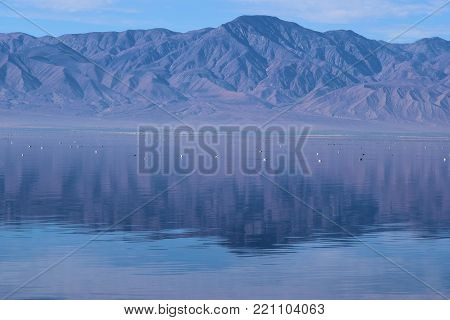 Low lying layer of haze above a desert lake surrounded by barren mountains taken in the Salton Sea, CA