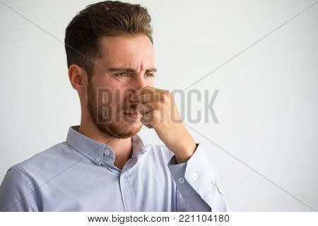 Portrait of displeased young Caucasian businessman wearing shirt pinching nose. Disgust and bad smell concept poster