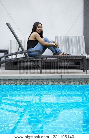 Black female resting by the hotel or resort pool.  The solo tourist is on vacation by herself to have time alone for leisure.  The image depicts tourism or a relaxing spa.  The blue water provides copy space.