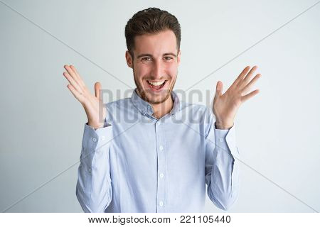 Portrait of excited young Caucasian businessman wearing shirt clapping hands, looking at camera and smiling. Success and bargain concept