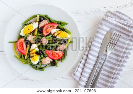 Summer warm salad with cooked green beans, tuna, tomatoes, boiled eggs and sauce balsamico glassa in white plate with knife and fork on wooden background. Healthy eating concept. Top view.