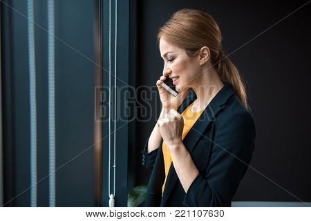 Side view beaming lady telling by phone while standing in apartment. Conversation and job concept