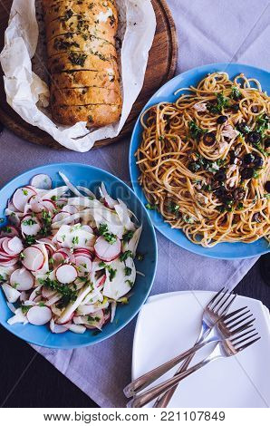 Traditional Italian dinner - Spaghetti Alla Puttanesca pasta with black olives, tuna, anchovies, capers and parsley, vegetable salad and baked ciabatta. Vegetarian food. Italian cuisine. Top view.