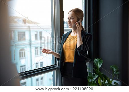 Portrait of happy businesswoman telling by mobile while standing near window in modern apartment. Conversation and labor concept