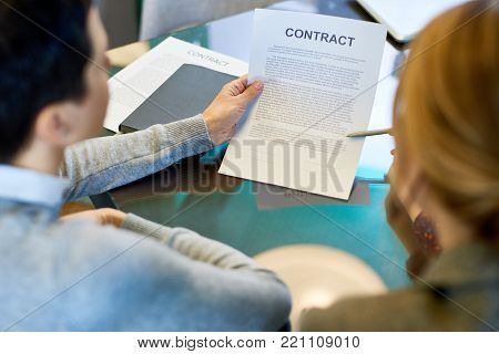 Over shoulder view of unrecognizable business partners in formalwear studying contract before signing it