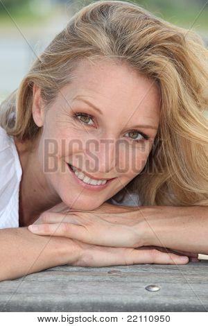A close up of eine Frau mittleren Alters, die bei uns lächelnd.