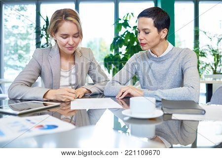 Group portrait of confident white collar workers gathered together at spacious boardroom and studying statistic data with interest