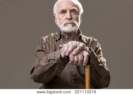 Life passing by. Portrait of serious male pensioner sticking with a cane. Focus on hands. Isolated on grey background