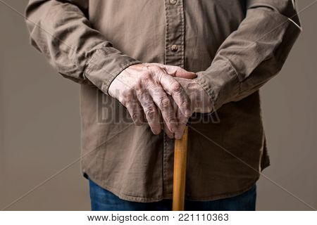Arms of old man on waking stick. Isolated on grey background. Close up