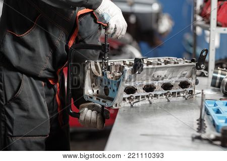 the mechanic installs a new valve. Disassemble engine block vehicle. Motor capital repair. Sixteen valves and four cylinder. Car service concept