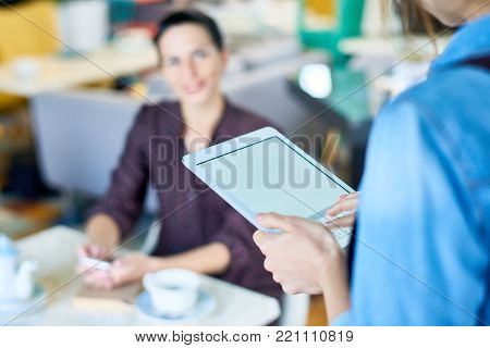 Unrecognizable waitress using digital tablet while taking order from pretty client at restaurant, focus on foreground