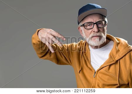 Portrait of serious male pensioner in modish clothes showing rap sign. Isolated on grey background