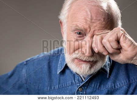 Portrait of upset old man rubbing his eye while crying. Isolated on grey background