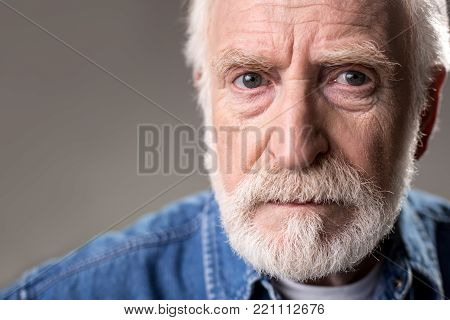 Close up of severe hoary man staring at camera. Copy space in left side. Isolated on grey background