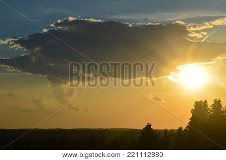 Sun behind a cloud at sunset in Upstate New York